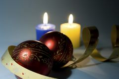 Holiday. Xmas balls and candles on blue background Stock Photos