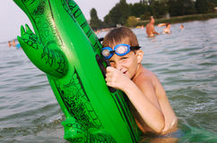 Holiday. Young boy hold his green floater crocodile in the water Royalty Free Stock Images