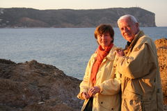 On holiday. Elderly couple standing close to the sea near some rocks Royalty Free Stock Photography