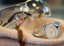 Sunglasses and wrist watches Placed on a light brown hat.  Stock Photography