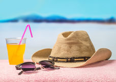 Holiday adventure and summer vacation concept with essential equipment. Brimmed hat, sunglasses and yellow delicious beverage. royalty free stock photo