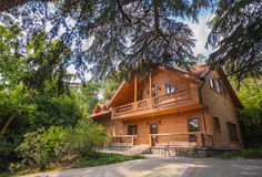 Holiday apartment - wooden cottage. In summer forest Royalty Free Stock Photo