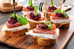 Holiday appetizers with cranberry sauce on a wooden server Stock Image