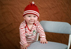 Holiday baby. Nine month old standing wears a festive outfit Stock Photos