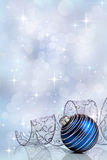 Holiday background with a blue Christmas ornament and ribbon. Holiday background with a blue Christmas ornament and curled ribbon against a festive background royalty free stock image