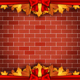 Holiday background on brick wall with autumn leaves and red bow. Royalty Free Stock Photography