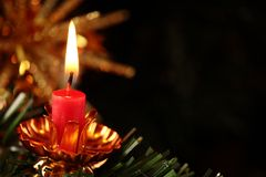Holiday background. Burning candle on branch with black copy space stock photos