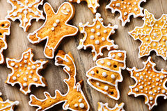 Holiday background with gingerbread cookies over wooden table Royalty Free Stock Images