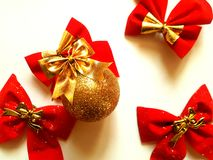 Holiday background with glitter ball and bows. Holiday background with golden christmas ball and red velvet bows isolated on white Royalty Free Stock Photos