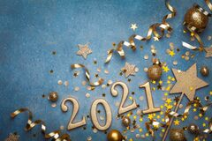 Holiday background with golden Christmas decorations and New year 2021 numbers and confetti top view