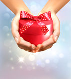 Holiday background with hands holding gift box. Stock Photos