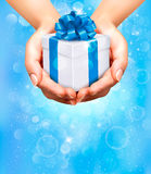 Holiday background with hands holding gift boxes. Royalty Free Stock Photo