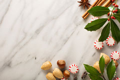 Holiday background with peppermint candy. Nuts and spices on marble Royalty Free Stock Image