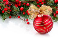 Holiday background with red Christmas ornament, golden bow, berries and fir branches. Holiday background with a red Christmas ornament and golden bow and Royalty Free Stock Images