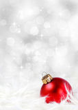 Holiday background with red ornament on feathers Royalty Free Stock Image