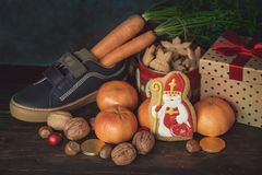 Saint Nicholas gifts and cookies. Holiday background Saint Nicholas, Sinterklaas, with children shoe with carrots, cookies, nut, tangerines, gifts and sweets stock photography