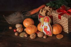 Saint Nicholas gifts. Holiday background Saint Nicholas, Sinterklaas, with traditional dutch shoe with carrots, cookies, nut, tangerines, gifts and sweets royalty free stock image