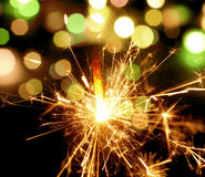 Holiday background with a sparkler. Royalty Free Stock Images