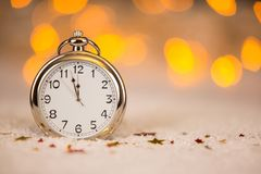 Holiday background with a sparkler and new year clock. New year working Royalty Free Stock Images