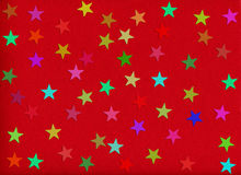 Holiday background. stars on red rough paper. Holiday background. confetti in shape of star on red rough paper Stock Images