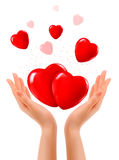 Holiday background with two hands and red hearts. Stock Photography