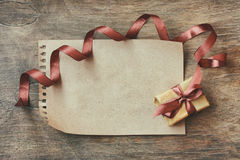 Holiday background wrapped gift box, brown silk ribbon Stock Image