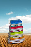 Holiday baggage on beach. Bright colorful cases on a golden sandy beach with a bright blue summer sky Royalty Free Stock Images