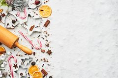 Holiday baking background. For baking Christmas cookies with cutters, rolling pin, candy cane and spices on white marble table covered with snow. Top view with stock photos