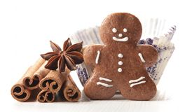 Holiday baking. Close-up of gingerbread man, vanilla beans, anise stars, cinnamon sticks in paper cupcakes on white background stock image