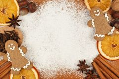 Holiday baking frame with gingerbread men, nuts and spices Stock Photos