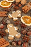Holiday baking ingredients and gingerbread men on rustic wood Stock Photo