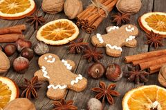 Holiday baking ingredients and gingerbread men on rustic wood Royalty Free Stock Photos