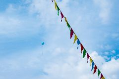 Holiday, balloons rushing up, colorful flags. Colored balloons, Holiday, balloons rushing up, colorful flags. Against the blue sky stock photography