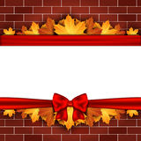 Holiday banner on brick wall with autumn leaves and red bow. Stock Photography