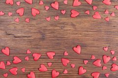 Holiday banner or frame for Valentines day. Red hearts on vintage wooden background top view. Space for greeting text. royalty free stock photo