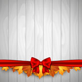 Holiday banner on wooden wall with autumn leaves and red bow. Autumn background. Stock Photo