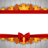 Holiday banner on wooden wall with autumn leaves and red bow. Autumn background. Royalty Free Stock Photo