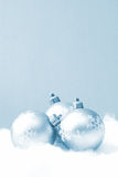 Holiday Baubles. Three holiday baubles on some fake snow and coloured in blue monochrome stock images
