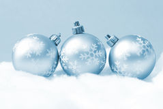 Holiday Baubles. Three holiday baubles on some fake snow and coloured in blue monochrome stock photo