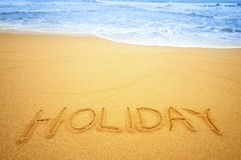 Holiday on the beach. Holiday written in the sand on the beach blue waves in the background Stock Images