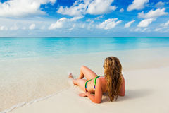 Holiday at the beach paradise Caribbean islands. Young girl lies on the beach on the Caribbean Sea turquoise Maldivian Bahamas Hawaii stock photography