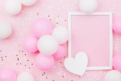 Holiday or birthday mockup with frame, pastel balloons, heart and confetti on pink table top view. Flat lay composition. Holiday or birthday mockup with frame royalty free stock image