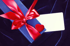 Holiday blue gift box with red ribbon Royalty Free Stock Image
