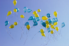Holiday blue and yellow balloons in the blue sky. Holiday blue and yellow flying balloons in the blue sky Royalty Free Stock Photography