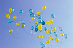Holiday blue and yellow flying balloons in the blue sky Stock Image