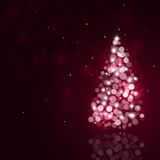 Holiday Bokeh Christmas Tree. Winter holiday christmas greeting background with snow fir tree and blurry lights Stock Photography