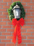 Holiday bow around an outdoor light Royalty Free Stock Images