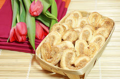 Holiday breakfast. Wicker basket with pastries and tulips on background Royalty Free Stock Photography
