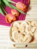Holiday breakfast. Wicker basket with pastries and tulips on background Stock Image