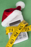 Holiday on a Budget. Calculator with a Santa Hat squeezed by a measuring tape representing a tight holiday budget Royalty Free Stock Images